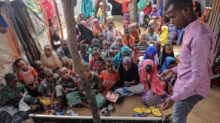 L'étudiant universitaire Yahye Mohamed apprend à lire, écrire et compter aux enfants et adolescents somaliens déplacés, en tant qu'enseignant bénévole dans une école de fortune au camp de Badbado à Mogadiscio, en Somalie, le 25 juin 2018. (Mohamed ABDIWAHAB / AFP)