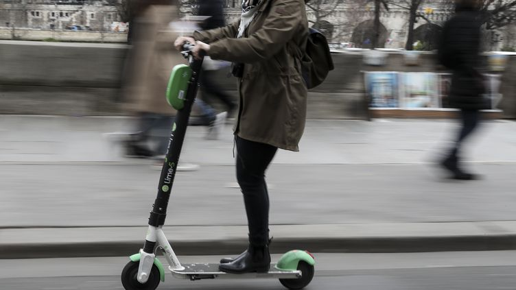 Une femme sur une trottinette électrique, à Paris. (KENZO TRIBOUILLARD / AFP)