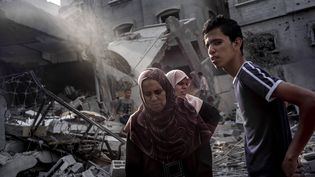 Des Palestiniens devant un immeuble détruit par un bombardement israélien, le 24 juillet 2014, à Jabalia. (MARCO LONGARI / AFP)