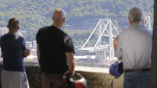 Le 15 août 2018, des habitants de Gênes (Italie) observent le pont quis'est effondré la veille, faisant au moins 39 victimes. (MAXPPP)