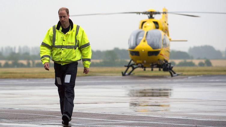 Le Prince William et unhélicoptère-ambulance de la compagnieEast Anglian Air Ambulance, pour laquelle il est pilote, le 13 juillet 2015 à l'aéroport de Cambridge. (REUTERS)