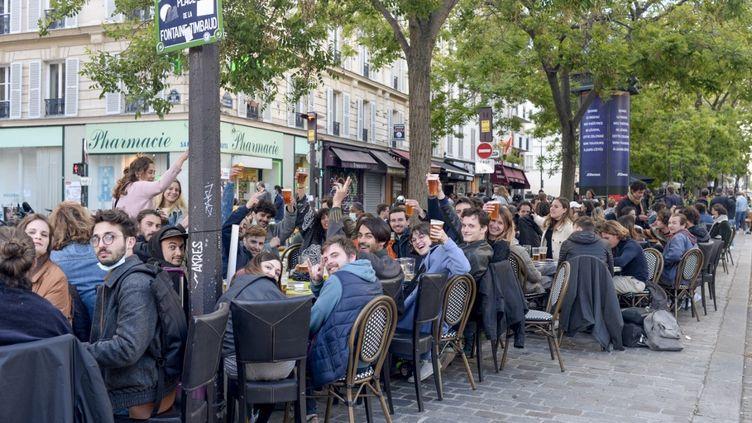 Des Parisiens profitent de la réouverture des terrasses des bars et restaurants, à Paris, le 19 mai 2021. (REMI DECOSTER / HANS LUCAS / AFP)