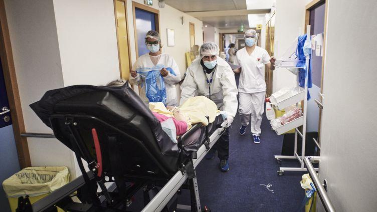 Des ambulanciers transfèrent une nouvelle patiente dans l'une des deux unités Covid-19 de l'Institut Mutualiste Montsouris, le 6 mai 2021 à Paris. (ANTONIN BURAT / HANS LUCAS / AFP)