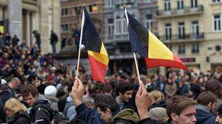 Des Belges brandissent des drapeaux place de la Bourse à Bruxelles, le 23 mars 2016. (CITIZENSIDE /OLIVIER GOUALLEC / AFP)