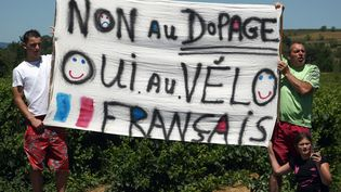 Des supporters français brandissent une bannière le long de la route du Tour de France, le 18 juillet 2008, près de Nîmes. (JOEL SAGET / AFP)