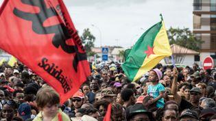 Des manifestants défilent à Cayenne, brandissant le drapeau de la Guyane, le 28 mars 2017. (JODY AMIET / AFP)