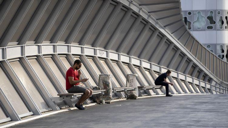 Deux personnes profitent d'une sortie durant le premier confinement, le 20 avril 2020 à Paris. (FRANCK RENOIR / HANS LUCAS / AFP)