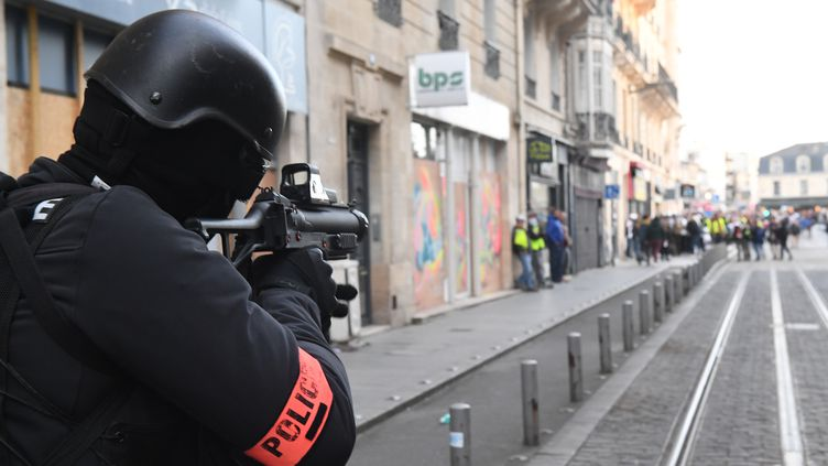 Un policier braque un LBD vers des manifestants, le 2 mars 2019, à Bordeaux (Gironde). (MEHDI FEDOUACH / AFP)