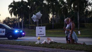Deux Américaines prient pour les 17 morts de la fusillade dans le lycée deMarjory Stoneman Douglas de Parkland, en Floride (Etats-Unis), le 17 février 2018. (AFP)