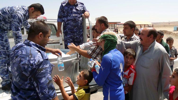 Des militaires irakiens distribuent de l'eau à des civils kurdes, vendredi 8 août 2014 sur la route reliant Kirkouk à Arbil (Irak). (MARWAN IBRAHIM / AFP)