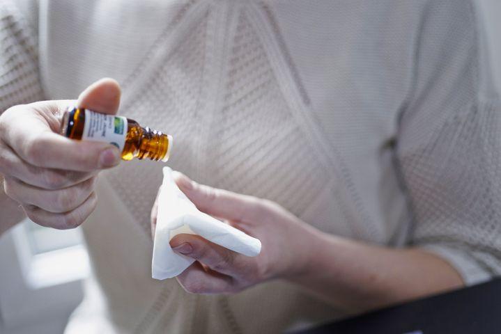 Photo d'illustration. Une personne verse quelques gouttes d'huile essentielle sur un mouchoir. (ALICE S. / BSIP / AFP)