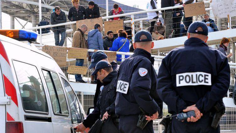 Des policiers font face à des migrants syriens qui bloquent une passerelle du terminal ferry de Calais (Pas-de-Calais), le 3 octobre 2013. (PHILIPPE HUGUEN / AFP)