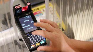 Un client paie ses courses par carte bancaire en Allemagne. (DANNY GOHLKE / DPA)
