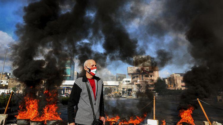 Un homme portant un masque représentant le drapeau libanaissur un barrage routier mis en place par des manifestants à Beyrouth, au Liban, le 8 mars 2021. (ANWAR AMRO / AFP)