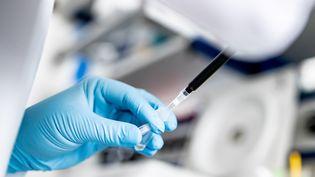 Un chercheur manipule un échantillon dans le cadre de travaux sur le Covid-19, le 20 mai 2020, à Düsseldorf (Allemagne). (MARCEL KUSCH / DPA / AFP)