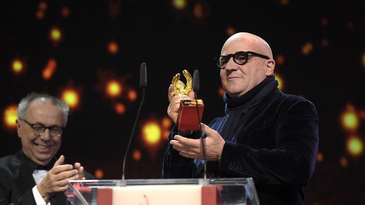"""Le réalisateur italien Gianfranco Rosi reçoit l'Ours d'or pour son film """"Fuocoammare"""", samedi 20 février 2016 à Berlin (Allemagne). (TOBIAS SCHWARZ / AFP)"""