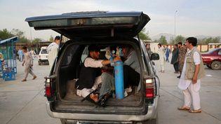 Un homme blessé attend d'être transporté à l'hôpital, le 8 mai 2021, après une explosion devant une école à Kaboul (Afghanistan). (ZAKERIA HASHIMI / AFP)