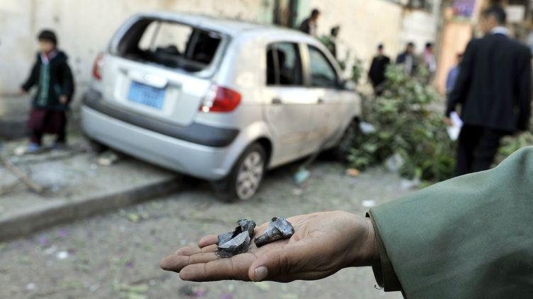 Un soldat yéménite montre des éclats après l'explosion d'un obus de mortier visant l'ambassade de France, à Sanaa, le 3 février 2014. (MOHAMMED HAMOUD / ANADOLU AGENCY / AFP)