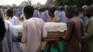 Un groupe d'hommes enterre une victime de l'attaque de Boko Haram dans le village de Lawanti (nord-est du Nigeria) le 20 février 2019. (AUDU ALI MARTE / AFP)