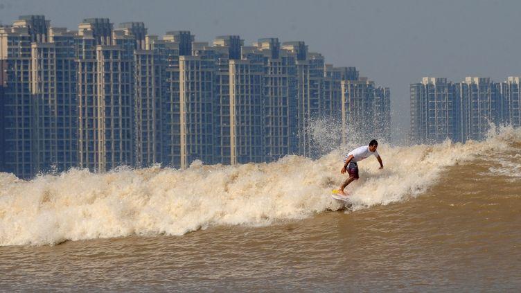 Un surfeur sur le mascaret du fleuve Qiantang à Hangzhou, province du Zhejiang,est de la Chine, le 15 septembre 2011. (HAN CHUANHAO / XINHUA / AFP)