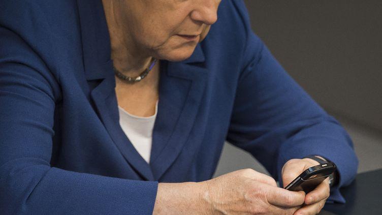 La chancelière allemande Angela Merkel tape sur son téléphone alors qu'elle se trouve au Bundestag (la chambre des députés allemande) à Berlin, le 3 juillet 2015. (ODD ANDERSEN / AFP)