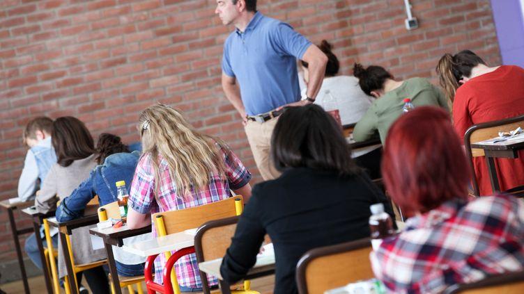 Un enseignant entouré d'élèves lors de l'épreuve de philosophie du baccalauréat, le 17 juin 2015 à Lambersart (Nord). (THIERRY THOREL / CITIZENSIDE / AFP)