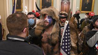 """Jacob Anthony Chansley, le """"chaman QAnon"""", le 6 janvier 2021, face à un policier lors de l'envahissement du Capitole par des partisans de Donald Trump à Washington. (SAUL LOEB / AFP)"""