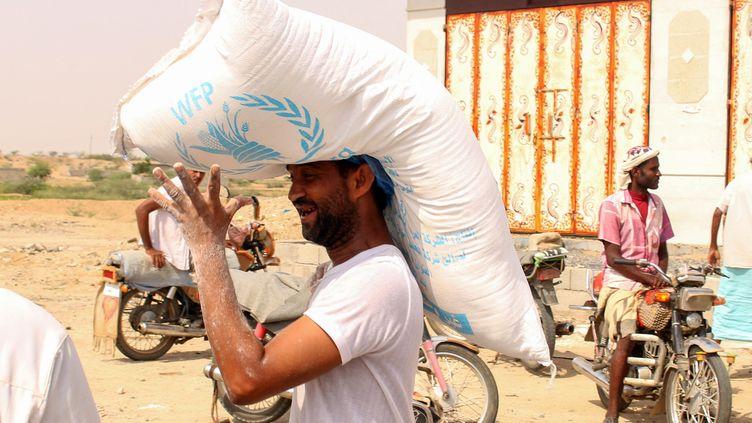 Un Yéménite transporte l'aide alimentaire du Programme alimentaire mondial. (ESSA AHMED / AFP)