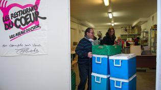 Des bénévoles des Restos du Coeur transportent des denrées dans un entrepôt à Tours (Indre-et-Loire). (GUILLAUME SOUVANT / AFP)