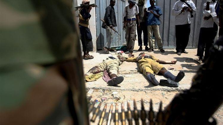 Des miliciens de Al-Chabaab regardent les corps de deux policiers tués le 13 juillet. (AFP)