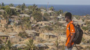Un jeune mozambicain regarde les habitations à flanc de colline à Pemba, ville portuaire de Cabo Delgado dans le nord-est du Mozambique, en décembre 2020. (ALFREDO ZUNIGA / AFP)
