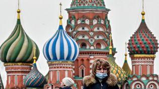 Une femme masquée devant la cathédrale Saint-Basile de Moscou (Russie), le 22 mars 2021. (YURI KADOBNOV / AFP)