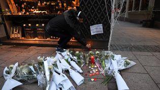 Un homme allume une bougie en hommage aux victimes d'une fusillade dans le centre-ville de Strasbourg, le 12 décembre 2018. (PATRICK HERTZOG / AFP)