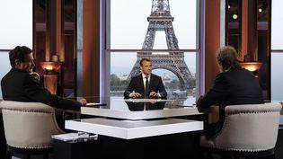 Le président de la République, Emmanuel Macron interrogé par Jean-Jacques Bourdin (de dos à droite) et par Edwy Plenel ((de dos à gauche), le 15 avril 2018. (FRANCOIS GUILLOT / POOL)
