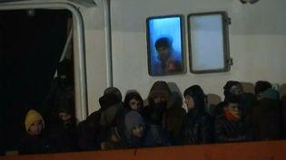 Des migrants clandestins à bord d'un cargo ramené par la marine italienne à Gallipoli (Italie), le 31 décembre 2014. (APTN)