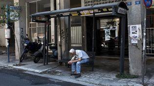 Un homme attend à un arrêt de bus, le 12 juillet 2015 à Athènes (Grèce). (ANGELOS TZORTZINIS / AFP)