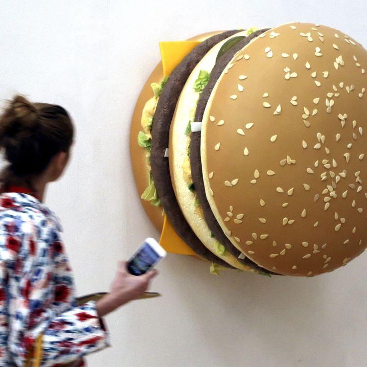 """Une femme observe la création """"Big Big Mac"""" de Tom Friedman lors d'une exposition installée à Milan dans le cadre de l'Exposition 2015, le 8 avril 2015. (STEFANO RELLANDINI / REUTERS)"""
