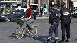 Une femme circule à vélo, le 23 mars 2015, à Paris. (FRANCOIS GUILLOT / AFP)