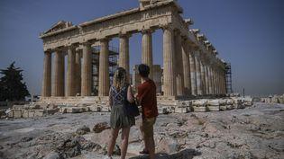 Des touristes devant l'Acropole à Athènes (Grèce). (ARIS MESSINIS / AFP)