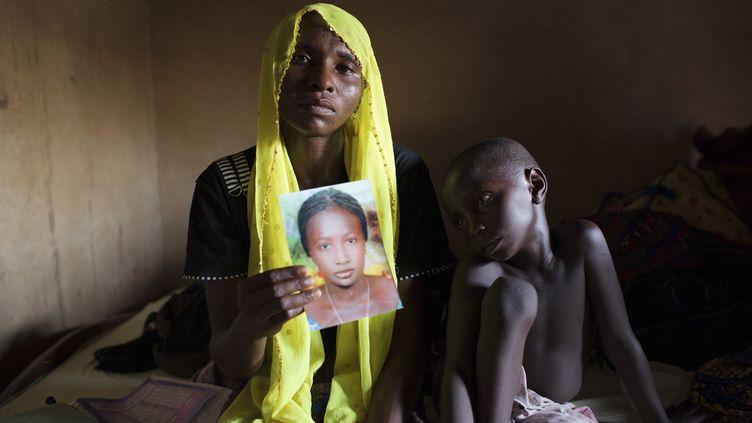 Une femme montre le portrait de sa fille, enlevée par Boko Haram en avril, àMaiduguri, dans le nord-est du Nigeria, le 21 mai 2014. (JOE PENNEY / REUTERS)