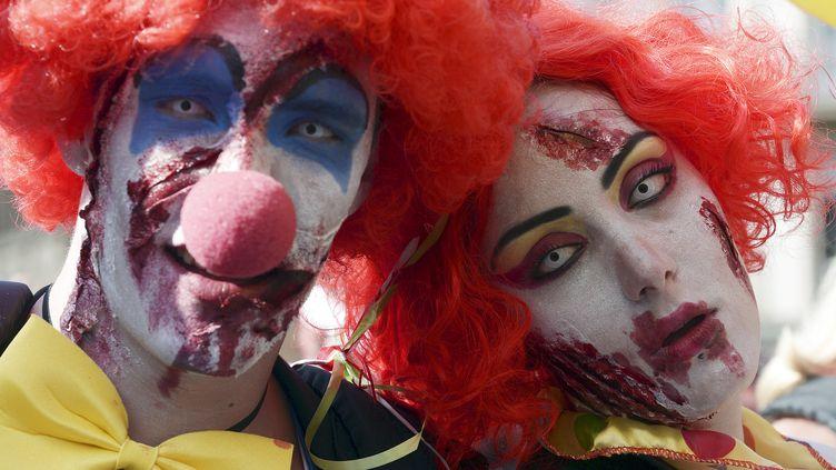 """Deux personnes déguisées en clowns zombies participent à la """"Zombie Walk"""" à Strasbourg (Bas-Rhin), le 13 septembre 2014. (FREDERICK FLORIN / AFP)"""