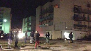 Des riverains face à dse policiers dans le quartier de la Croix Rouge, à Reims (Marne), dans la nuit du 7 au 8 janvier 2015. (CHARLES-HENRY BOUDET / FRANCE 3 CHAMPAGNE-ARDENNE)