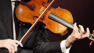 """Le violonniste américain David AAron Carpenter joue du Stradivarius """"Macdonald"""", créé en 1719 par Antonio Stradivari (1641-1737) à la maison de vente Sotheby's à Paris, le 15 avril 2014. Sotheby's a annoncé la vente du violon au printemps 2014 pour 45 millions de dollars.  (BERTRAND GUAY / AFP)"""