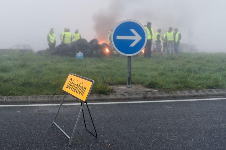 """Au rond-point de Carbonne (31) une trentaine de manifestants des """"gilets jaunes"""" avec des tracteurs filtrent les véhicules tout en brûlant quelques pneus et des slogans sur les tracteurs, en novembre 2018.  (Laurent Ferriere / Hans Lucas)"""