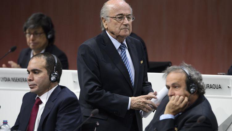Sepp Blatter passe devant le prince Ali et Michel Platini, au siège de la Fifa à Zurich (Suisse), le 29 mai 2015. (FABRICE COFFRINI / AFP)