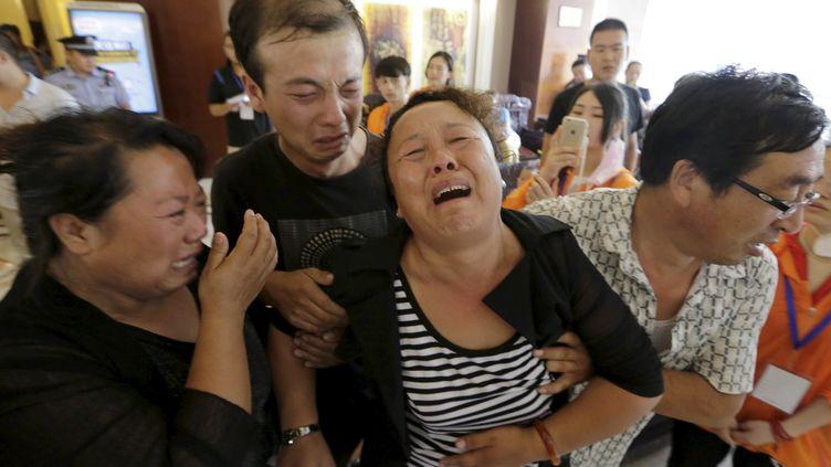 Des proches d'un pompier disparu à Tianjin (Chine) fondent en larmes, le 15 août 2015, en marge d'une conférence de presse des autorités dans la ville. (? JASON LEE / REUTERS / X01757)