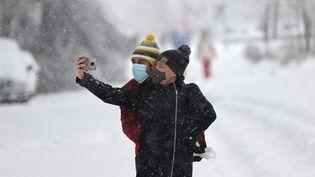 Deux personnes se photographient durant la tempête Filomena à Madrid, le 9 janvier 2021. (BURAK AKBULUT / ANADOLU AGENCY / AFP)