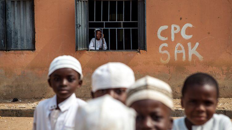 Un élève d'une école coranique regarde par une fenêtre tandis que d'autres jouent dans la cour à Kaduna, au Nigeria, le 21 janvier 2015. (FLORIAN PLAUCHEUR / AFP)