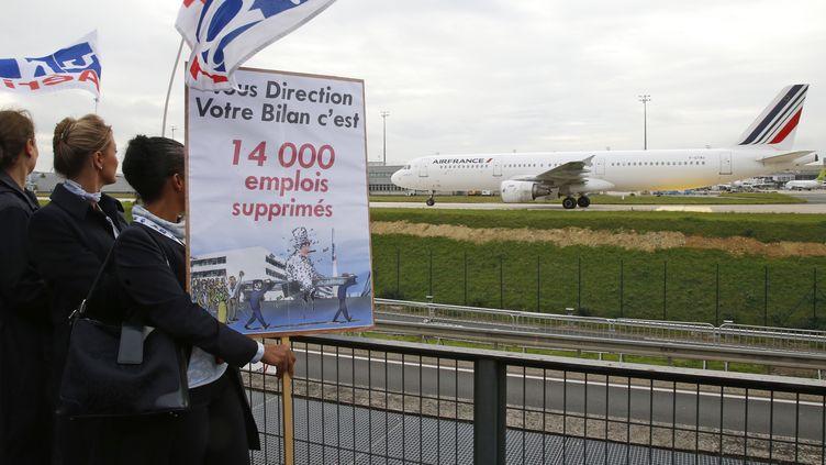 Des employés d'Air France manifestent au siège de la compagnie près de l'aéroport de Roissy alors qu'un avion de la compagnie passe sur le tarmac, le 5 octobre 2015. (JACKY NAEGELEN / REUTERS)