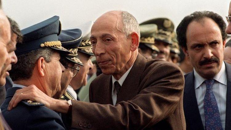 Mohamed Boudiaf (en civil au centre) salue le chef d'Etat major de l'armée, le général Abdelmalek Gueneizia (L), à l'aéroport d'Alger, le 16 janvier 1992, lors de son retour d'exil. (ABDELHAK SENNA / AFP)